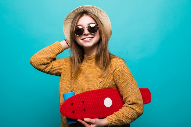 Portrait of young teen woman in sunglasses and hat holding skateboard while standing isolated over green wall