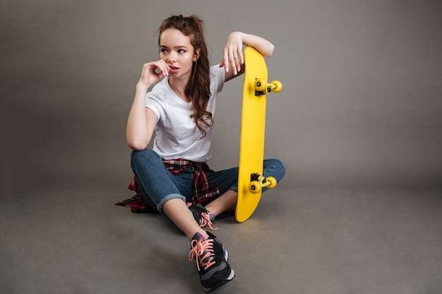 Portrait of a young teenage girl sitting with skateboard