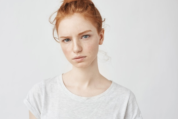 Portrait of young tender redhead woman with healthy freckled skin wearing grey top with serious expression.