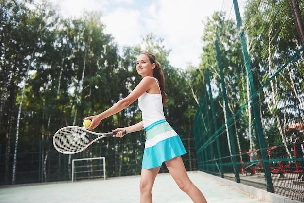 Ritratto di un giovane giocatore di tennis in piedi pronto per un servizio.