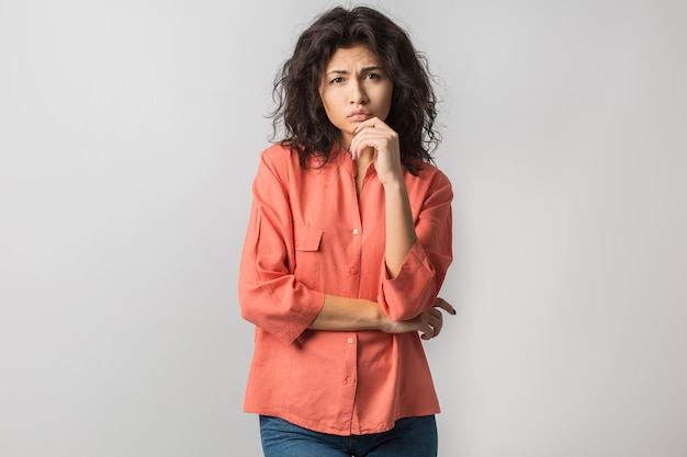 Portrait of young thoughtful brunette woman in orange shirt
