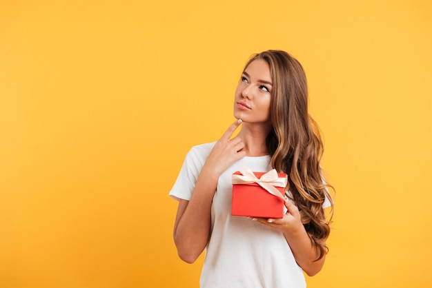 Portrait of a young thoughtful girl holding gift box