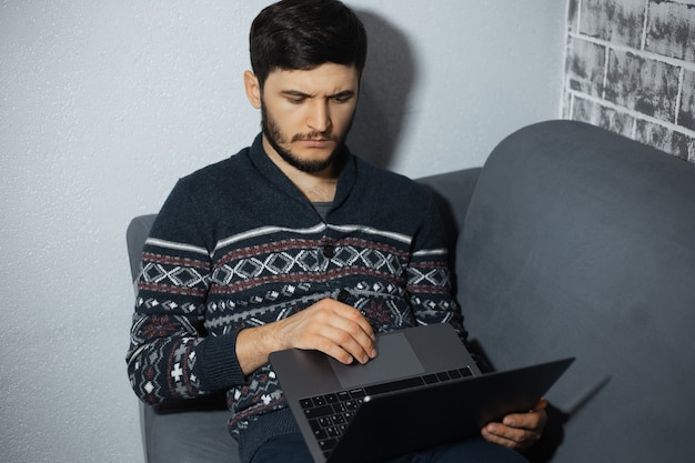 Portrait of young thoughtful man, working with laptop