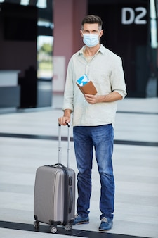 Portrait of young tourist in protective mask with luggage and tickets looking  while standing at the airport during pandemic