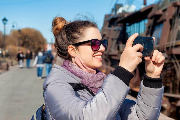 전화, 스탠드 및 상트페테르부르크 명소의 사진을 찍는 세로 젊은 관광 여자. 놀라운 여행과 잊을 수 없는 모험의 개념. 복사 공간