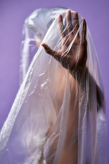 Portrait of young transgender with transparent plastic bag on body close up stop hand symbol