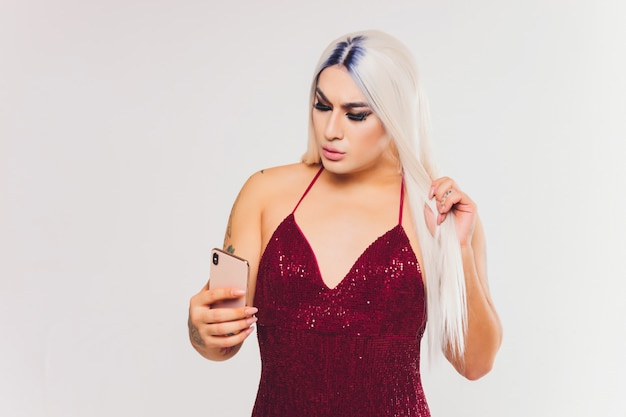 Portrait of young transgender woman on red dress with sequins looking at her smartphone