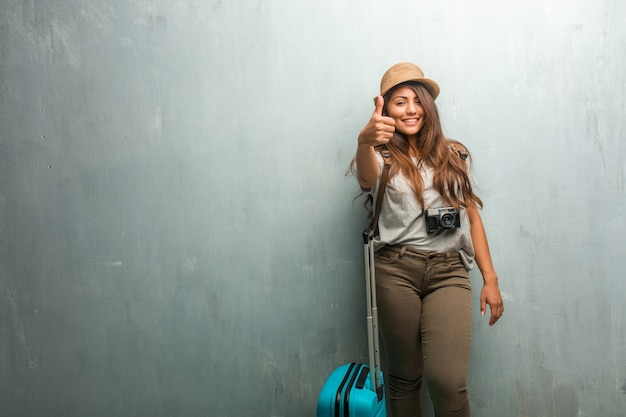 Portrait of young traveler latin woman against a wall cheerful and excited