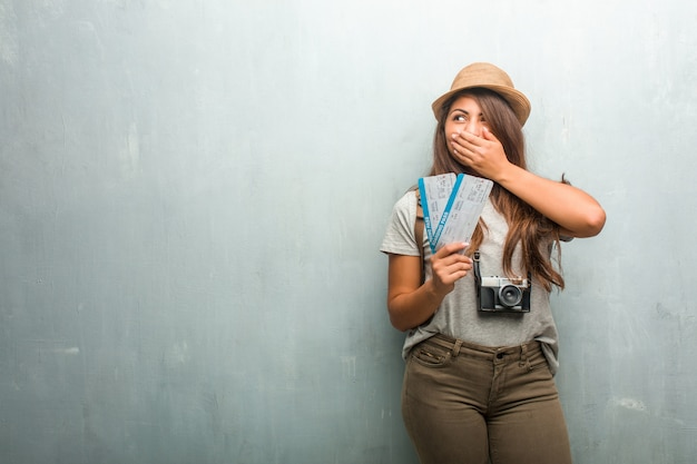 Portrait of young traveler latin woman against a wall covering mouth, symbol of silence and repression