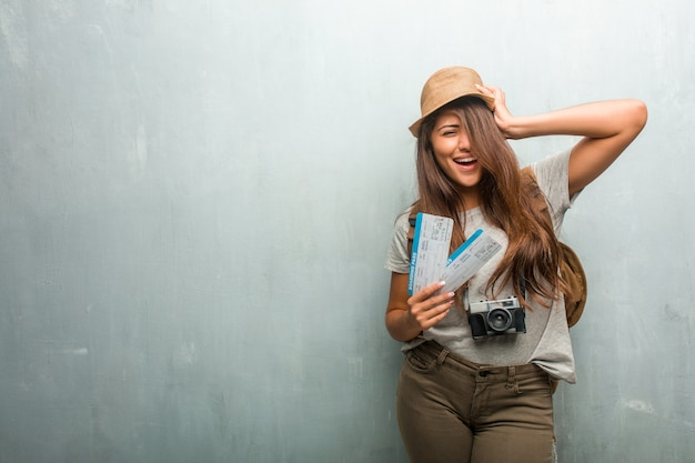 Portrait of young traveler latin woman against a wall frustrated and desperate