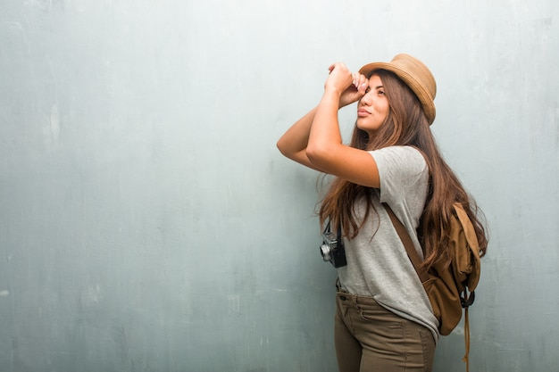 Portrait of young traveler latin woman against a wall looking through a gap, hiding and squinting