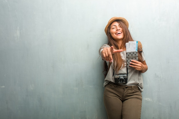 Portrait of young traveler latin woman against a wall shouting, laughing and making fun of another