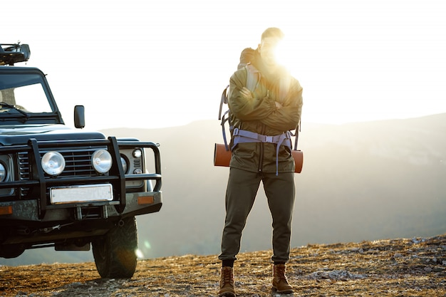 Portrait of a young traveler man in hiking equipment standing near his off-road car
