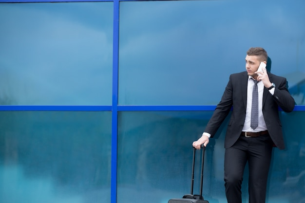 Portrait of young traveler in suit standing with suitcase and making call. copy space