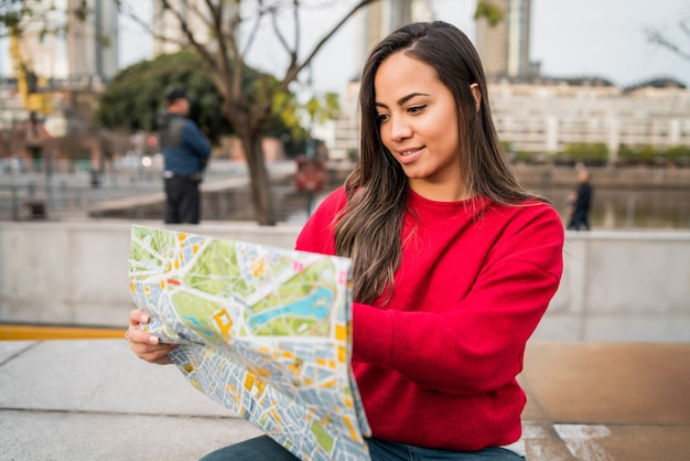 Portrait of young traveler woman holding a map and looking for directions outdoors in the street. travel concept.