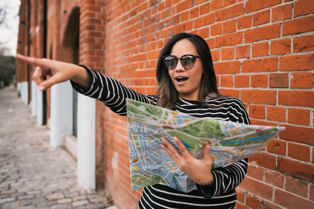 Portrait of young traveler woman holding a map, pointing somewhere and looking for directions outdoors in the street. travel concept.