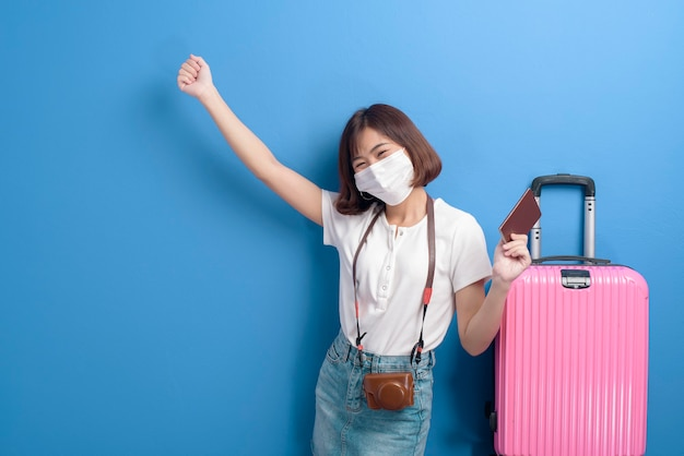 A portrait of young traveler woman with face mask , new normal travel concept