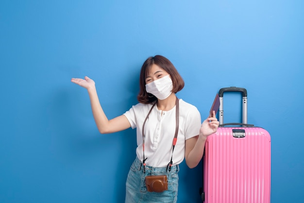 A portrait of young traveler woman with face mask, new normal travel concept