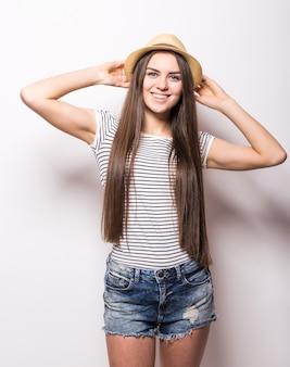 Ritratto di giovane donna alla moda che indossa jeans e cappello di paglia, isolato sul muro bianco