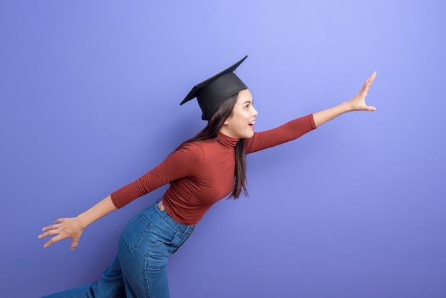 Portrait of young university student woman with graduation cap on violet background