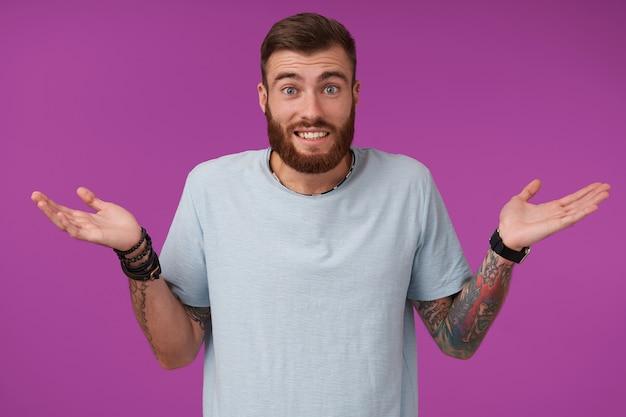 Ritratto di giovane uomo bruna tatuato non rasato che indossa la maglietta blu e accessori alla moda che contraggono la fronte e scrolla le spalle con i palmi sollevati, isolato su viola