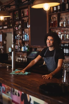Portrait of young waiter cleaning a counter