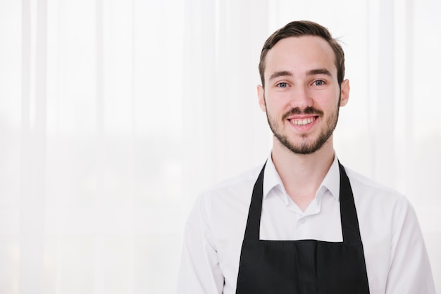 Portrait of young waiter looking at camera