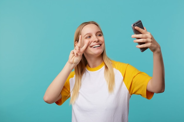 Ritratto di giovane donna dai capelli bianchi con trucco naturale che sorride ampiamente mentre fa selfie e solleva la mano con il segno di pace, isolato sull'azzurro