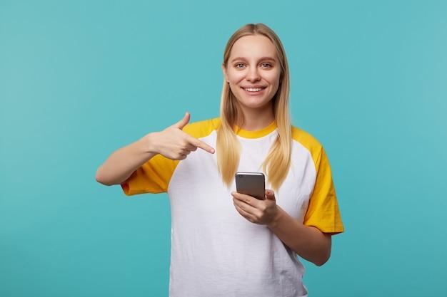 Ritratto di giovane donna dai capelli bianchi che mostra allegramente sul suo smartphone con la mano alzata con un sorriso affascinante, in posa sul blu