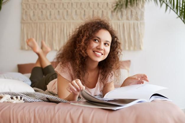 Ritratto di giovane donna afroamericana desiderosa con i capelli ricci, si trova sul letto e legge una rivista, sorride ampiamente, gode di una giornata di sole e sembra sognante allegra e felice.