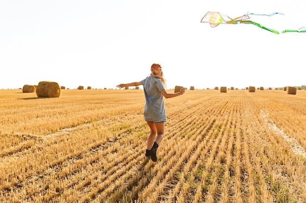Portrait of young woman 20s smiling and playing with flying kite during walk through golden field, during sunny day