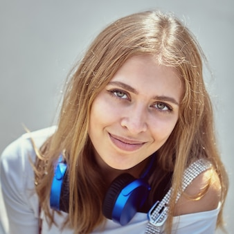 Portrait of young woman about 25 years old with long blond hair and earphones.