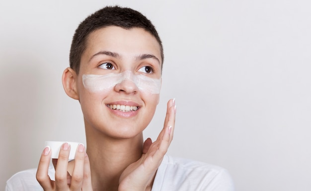 Portrait young woman applying cream on face
