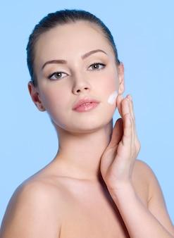 Ritratto di giovane donna che applica la crema sul suo bel viso fresco sull'azzurro