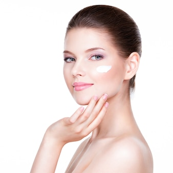 Portrait of young woman applying cream on her pretty face - over white background.