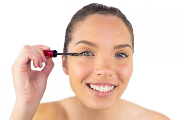 Portrait of young woman applying mascara to her eye