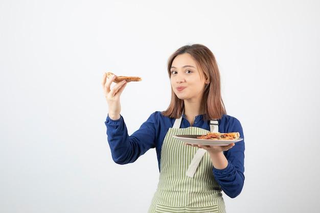 Ritratto di giovane donna in grembiule in posa con pizza su bianco