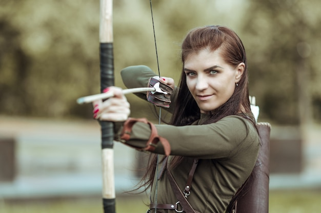 Portrait of young woman archery on forest background, close-up