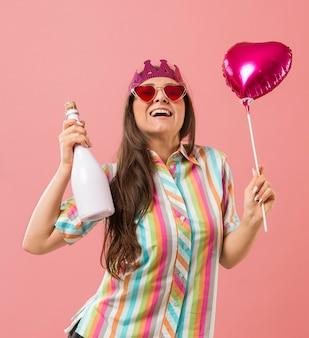 Портрет молодой женщины на вечеринке с воздушным шаром и бутылкой шампанского