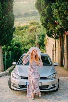 Portrait of young woman on background of modern car