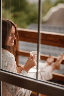 Portrait of young woman on the balcony holding a cup of coffee or tea in the morning. she in hotel room looking at the nature in summer. girl is dressed in stylish nightwear. relax time