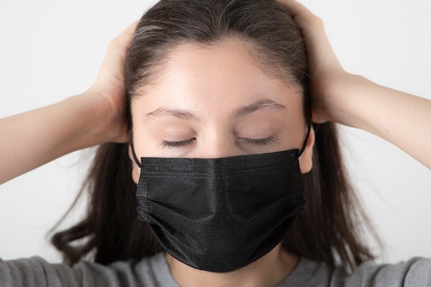 Portrait of young woman in black face mask holding her head. Free Photo