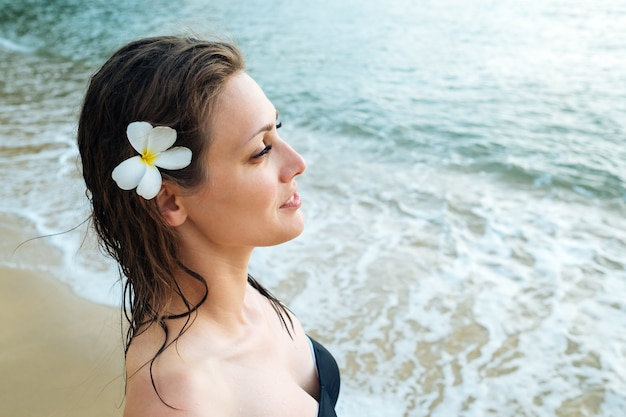 Portrait of young woman in black swimsuit on summer vacation