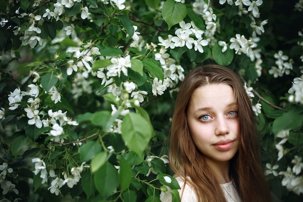 Portrait of young woman in blossoming spring tree, natural beauty