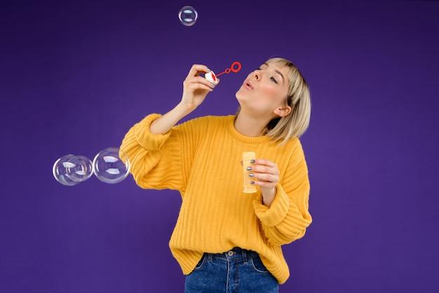 Il ritratto della giovane donna che soffia bolle sopra la parete porpora