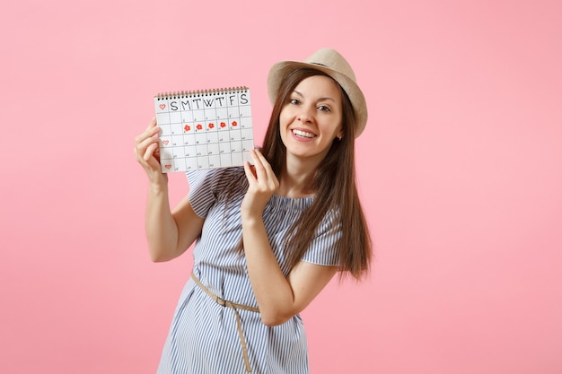 Portrait of young woman in blue dress, hat holding periods calendar for checking menstruation days isolated on bright trending pink background. medical, healthcare, gynecological concept. copy space.