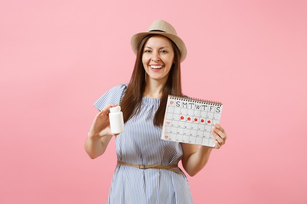 Portrait of young woman in blue dress holding white bottle with pills, female periods calendar, checking menstruation days isolated on background. medical healthcare gynecological concept. copy space.