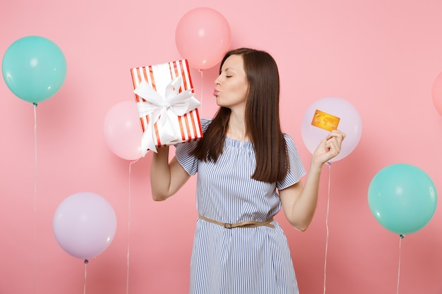 Portrait of young woman in blue dress kissing holding credit card and red box with gift present on pastel pink background with colorful air balloons. birthday holiday party, people sincere emotions.