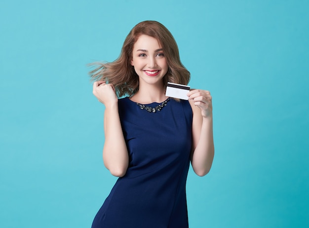 Portrait of a young woman in blue dress showing credit card and looking
