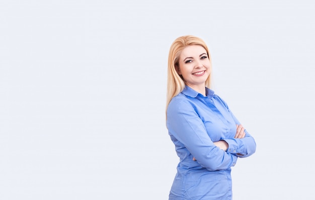 Portrait of young woman in blue shot with smile on her face on white, copy space.